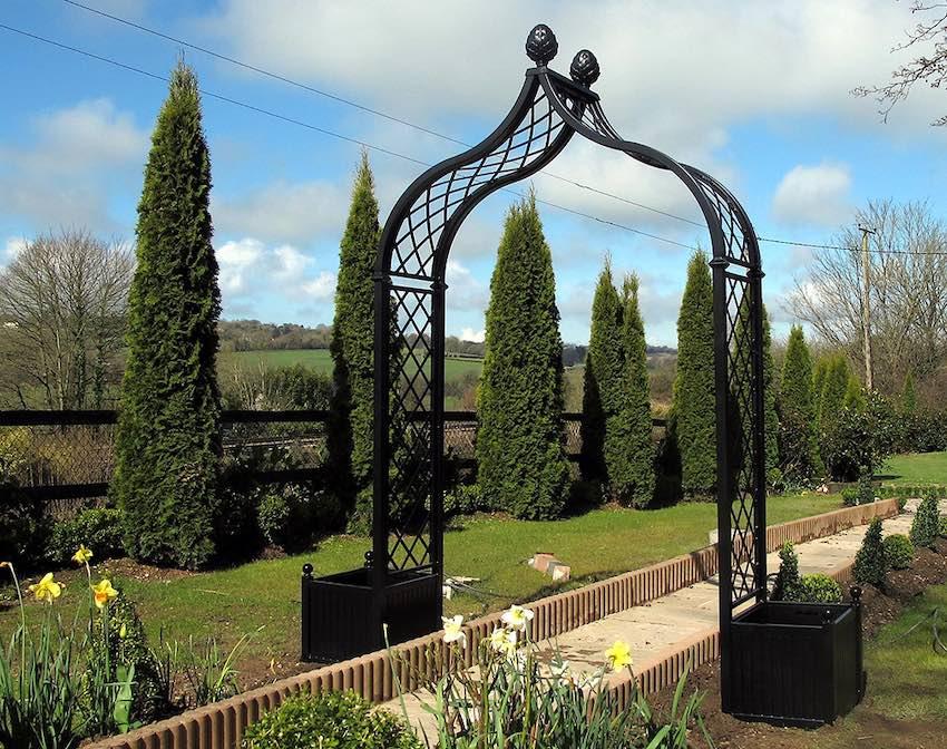 Metall-Rosenbogen-mit-Pflanzkübel-in-irischem-Garten