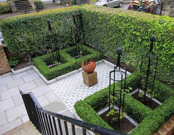 Four Metal Garden Obelisk I in formal patio garden